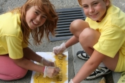 Teara Kinakin, left, and Camryn Koochin painting yellow fish along a storm drain in Grand Forks. Photo Erin Perkins.